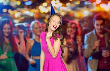people, holidays, night life and celebration concept - happy young woman or teen girl in pink dress and party cap at disco club over crowd lights background