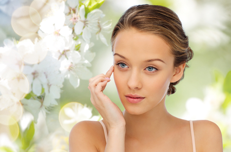 beauty, people, cosmetics, skincare and health concept - young woman applying cream to her face over green natural background with cherry blossom Stock Photo