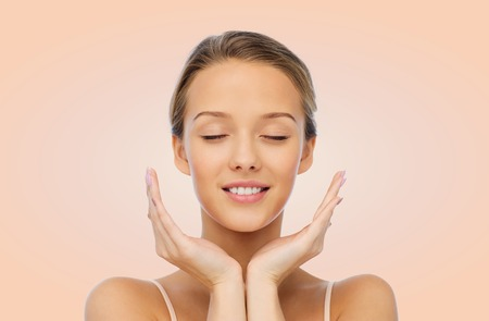 beauty eyes: beauty, people, skincare and health concept - smiling young woman face and hands over beige background