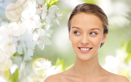 beauty, people and health concept - smiling young woman face and shoulders over green natural background with cherry blossom