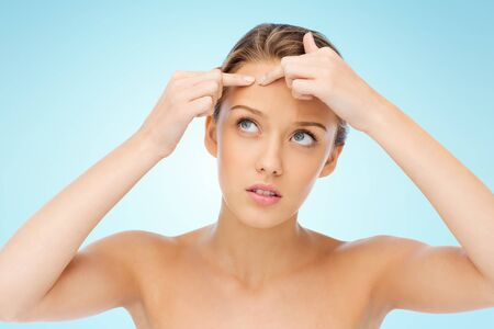 squeeze: beauty, people, skincare and health concept - young woman squeezing pimple on her face over blue background