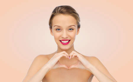 heart hands: beauty, people, love, valentines day and make up concept - smiling young woman with pink lipstick on lips showing heart shape hand sign over beige background