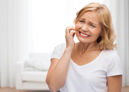 mensen, gezondheidszorg, dermatologie, allergie en skincare concept - ongelukkige vrouw die lijdt aan het gezicht inch op woonkamer achtergrond Stockfoto