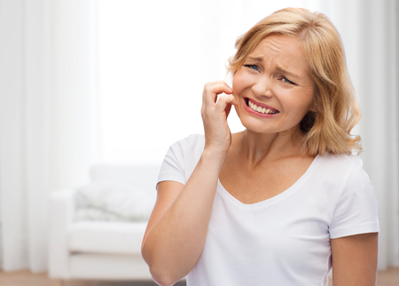allergic reaction: people, healthcare, dermatology, allergy and skincare concept - unhappy woman suffering from face inch over living room background