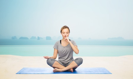 pranayama: fitness, sport, people and healthy lifestyle concept - woman making yoga meditation in lotus pose on mat over infinity edge pool at hotel resort background