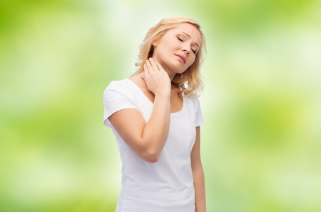 woman in pain: people, healthcare and problem concept - unhappy middle aged woman suffering from neck pain over green natural background