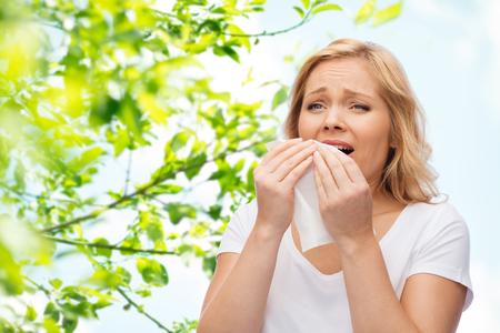 사람들, 건강 관리, 비염 및 알레르기 개념 - 녹색 자연 배경 위에 재채기 종이 냅킨 가진 불행 한 여자