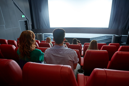 at the theater: cinema, entertainment, leisure and people concept - couple watching movie in theater from back
