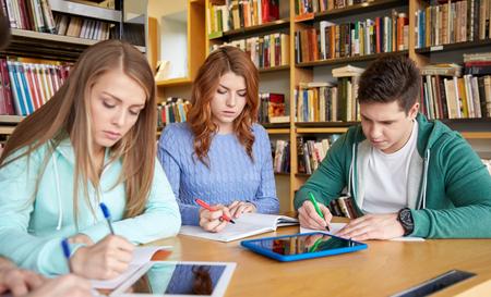 las personas, el conocimiento, la educación y la escuela concepto - grupo de estudiantes felices con las computadoras tablet pc escrito a los portátiles en la biblioteca
