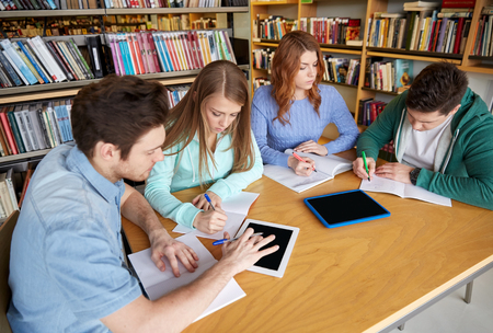people, knowledge, education and school concept - group of students with tablet pc computers writing to notebooks in library Stok Fotoğraf - 52989864