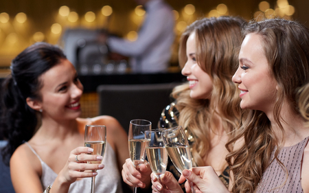SPARKLING WINE: celebration, friends, bachelorette party and holidays concept - happy women with champagne glasses at night club