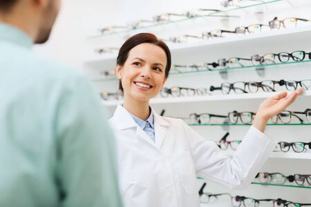 optical: health care, people, eyesight and vision concept - female optician showing glasses to man at optics store