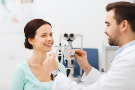 gezondheidszorg, geneeskunde, mensen, gezichtsvermogen en technologie concept - optometrist met pasbril die geduldige visie op ooghoogte kliniek of optiek winkel