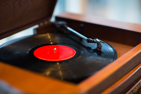 record: music, technology and object concept - close up of vintage record player with vinyl disc