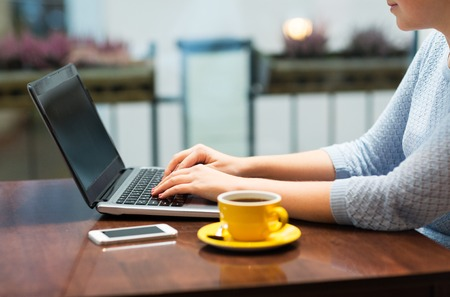 business lifestyle: business, people, technology and lifestyle concept - close up of woman typing on laptop with coffee and smartphone
