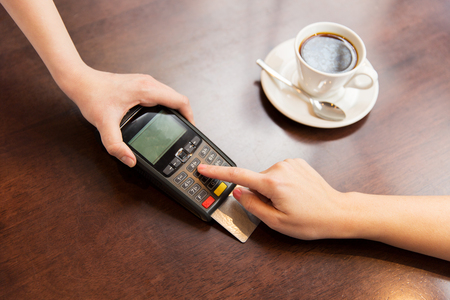 people, finance, technology and consumerism concept - close up of waitress holding credit card reader and customer hand entering pin code at cafe Stock Photo