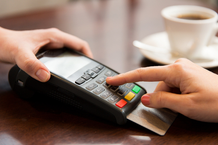 people, finance, technology and consumerism concept - close up of waitress holding credit card reader and customer hand entering pin code at cafe Standard-Bild