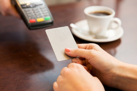 hand with card: people, finance, technology and consumerism concept - close up of waitress holding credit card reader and customer hand entering pin code at cafe Stock Photo