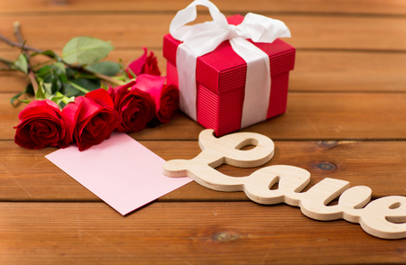birthday greetings: love, romance, valentines day and holidays concept - close up of gift box, red roses and greeting card with heart on wood