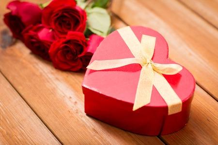 uprzejmości: miłość, data, romans, Walentynki i święta pojęcie - zamknąć w kształcie serca pudełko i czerwonych róż na drewnianym stole