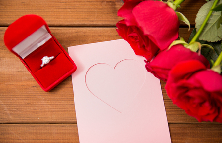 uprzejmości: love, proposal, valentines day and holidays concept - close up of gift box with diamond engagement ring, red roses and greeting card on wood Zdjęcie Seryjne
