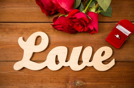flirtation: proposal, romance, valentines day and holidays concept - close up of gift box with diamond engagement ring, red roses and word love on wood Stock Photo