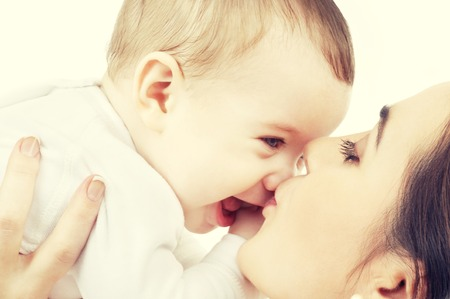 kisses: family and happy people concept - mother kissing her baby Stock Photo