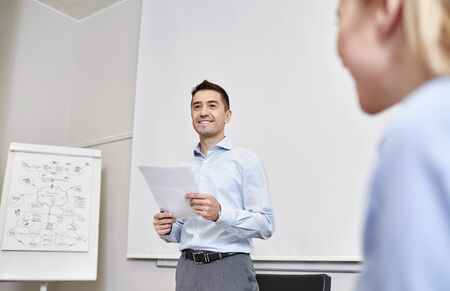 consulting room: business, people and planning concept - smiling businessman and woman with papers meeting on presentation in office Stock Photo