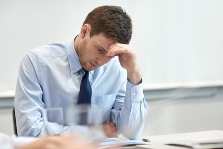 co workers: business, people and crisis concept - businessman sitting sad and solving problem in office
