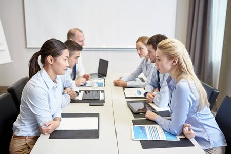 biznes, ludzie, kryzysu i konfrontacji koncepcji - uśmiechnięte działalności zespołu siedzi po przeciwnych stronach w biurze