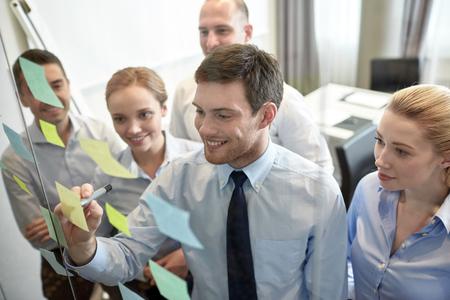 jovenes empresarios: negocios, personas, trabajo en equipo y la planificación concepto - sonriendo equipo de negocios con marcador y pegatinas que trabaja en oficina