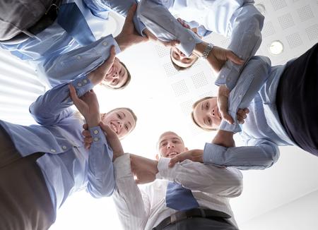 circulo de personas: negocio, la gente y el trabajo en equipo - concepto de grupo de hombres de negocios sonriente de pie en círculo y tomados de las manos el uno al otro Foto de archivo