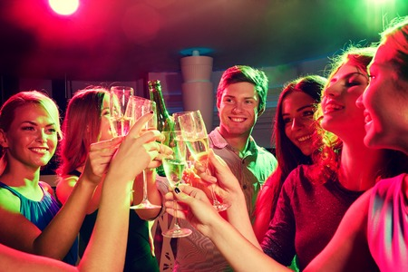beer wine: party, holidays, celebration, nightlife and people concept - smiling friends clinking glasses of champagne and beer in club Stock Photo