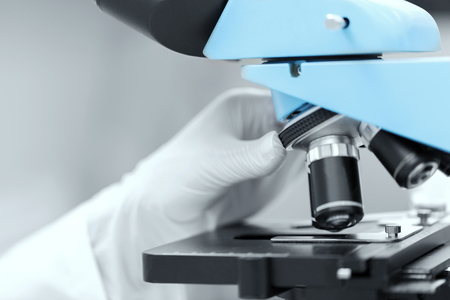 clinical: science, chemistry, biology, medicine and people concept - close up of scientist hand in glove setting microscope and making research in clinical laboratory