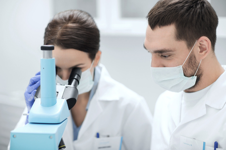 science, chemistry, technology, biology and people concept - young scientists in masks looking to microscope and making test or research in clinical laboratory Stock Photo - 53069572