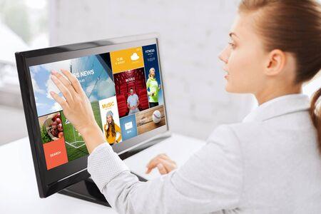 negocio, la gente, la tecnología y el concepto de medios de comunicación - mujer con páginas web sobre la pantalla táctil del ordenador en la oficina