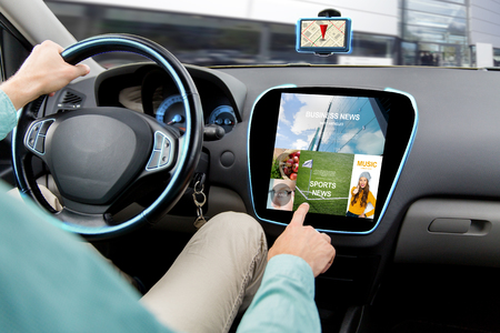 driving car: transport, road trip, technology, media and people concept - close up of man driving car and using news application on computer Stock Photo