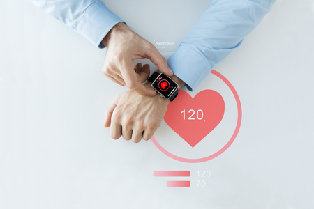 business, technology, health care, application and people concept - close up of male hands setting smart watch with red heart icon screen Banque d'images