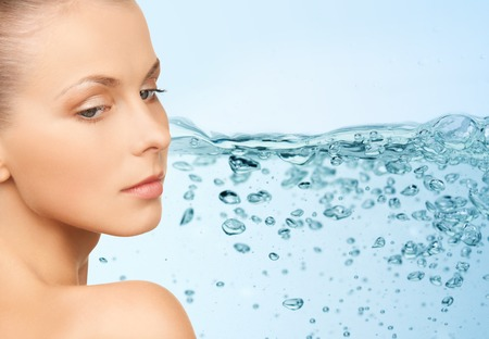 bare girl: beauty, people, moisturizing, body care and health concept - young woman face with bare shoulders over water splash background