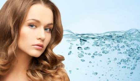 beauty, people, moisturizing, body care and health concept - young woman face with long shiny hair over water splash background
