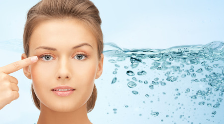 la beauté, les gens, l'hydratation, la vision et le concept de la santé - le visage d'une jeune femme pointant un doigt sur ses yeux sur les projections d'eau de fond Banque d'images