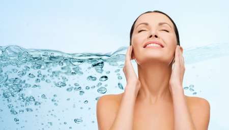 clarifying: beauty, people, skincare, moisturizing and health concept - smiling young woman cleaning her face over water splash on blue background