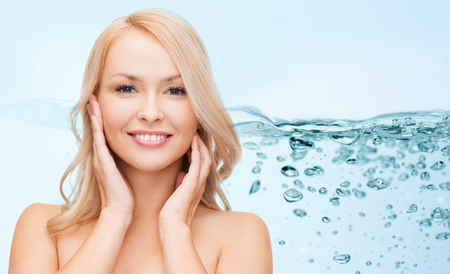 water concept: beauty, people, moisturizing and health concept - smiling young woman with bare shoulders touching her face over water splash on blue background Stock Photo