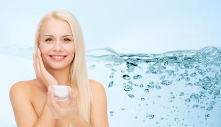 cosmetici, la salute e il concetto di bellezza - donna applicare la crema idratante per la pelle del viso Archivio Fotografico