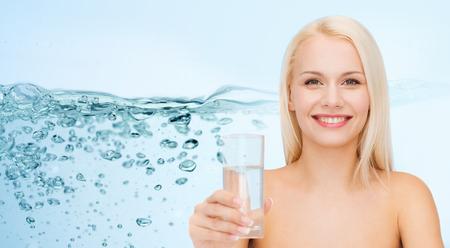 vaso con agua: Concepto de las personas, la salud y la belleza - cerca de la mujer sonriente joven con un vaso de agua sobre el chapoteo en fondo azul