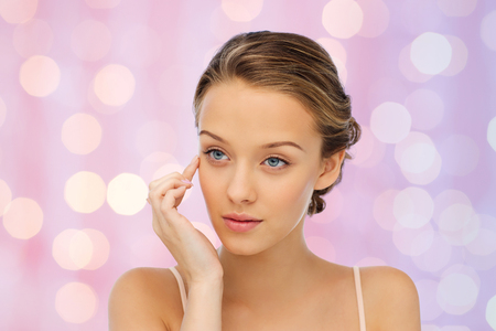 eye cream: beauty, people, cosmetics, skincare and health concept - young woman applying cream to her face over pink lights background Stock Photo