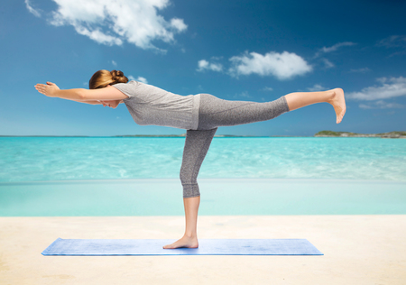 warrior pose: fitness, sport, people and healthy lifestyle concept - woman making yoga warrior pose on mat over beach background
