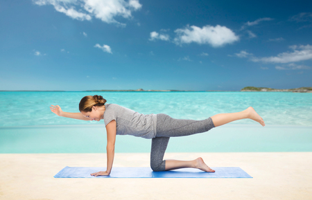 beach mat: fitness, sport, people and healthy lifestyle concept - woman making yoga in balancing table pose on mat over beach background Stock Photo