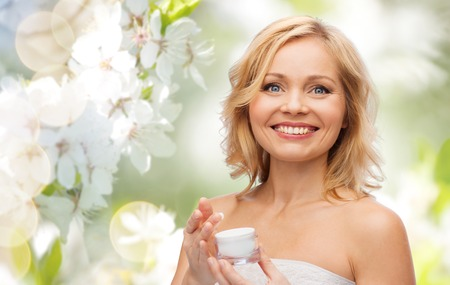 beauty, people, skincare and cosmetics concept - happy middle aged woman with cream jar over green natural background with cherry blossom