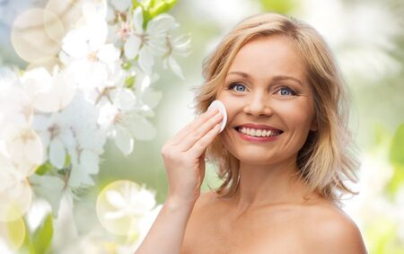 removing make up: beauty, people and skincare concept - happy middle aged woman cleaning face and removing make up with cotton pad over green natural background with cherry blossom